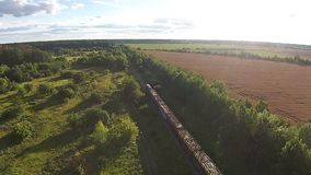 Aerial view on train laden with trees rides through the forest.  stock footage