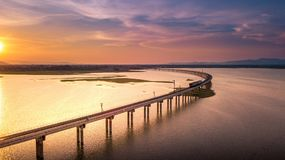 Aerial View The train is running on the bridge Over River Pa Sak. Dam Lopburi Thailand and Beautiful sunset Royalty Free Stock Photography