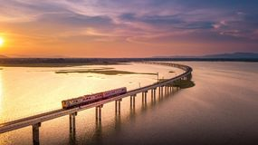 Aerial View The train is running on the bridge Over River Pa Sak. Dam Lopburi Thailand and Beautiful sunset Royalty Free Stock Photo
