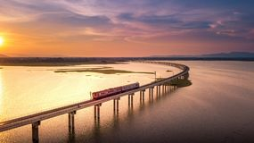 Aerial View The train is running on the bridge Over River Pa Sak. Dam Lopburi Thailand and Beautiful sunset Royalty Free Stock Images