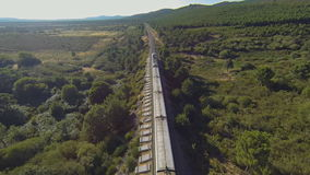 Aerial view of train running in the country, heading forward. Train running forward over railway in the forest at sunset, heading forward, aerial view stock video
