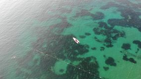 Aerial view transparent blue sea and a lone boat. stock video footage