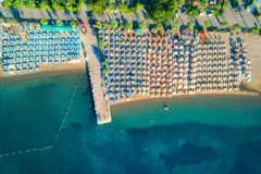Aerial view of transparent turquoise sea. Beautiful sandy beach with colorful chaise-lounges, boats, green trees, hotels, buildings at sunrise in Icmeler Stock Images