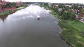 Aerial view of travel ship in river with green banks. Aerial view of ship travel in river stock footage