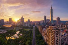 Aerial view of trees tunnel with park garden and skyscrapers buildings. Financial district and business centers in smart urban. City, Taipei at sunset, Taiwan royalty free stock images