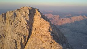 Aerial View of Triglav Peak at Sunrise, Julian Alps, Slovenia. Aerial view of Triglav peak with hikers on the top at sunrise, Julian Alps, Slovenia stock video footage