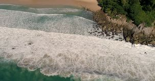Aerial view of tropical island beach and seashore. Aerial drone view of beautiful tropical island beach and waves crashing coastline cliff during sunny summer stock video