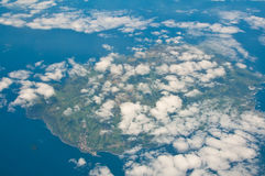 Aerial view of tropical island through the clouds. Island in the carribean seen from the air royalty free stock photography