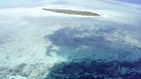 Aerial View of Tropical Island in Clouds in Indonesia. Shadows of clouds drift over a reef flat in Wakatobi National Park in Indonesia. This region harbors stock video