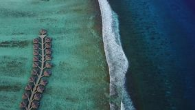 Aerial view of tropical island resort hotel with bungalows and turquoise Indian ocean waves on Maldives, view from above stock footage