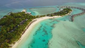 Aerial view of tropical island resort hotel with white sand palm trees and turquoise Indian ocean on Maldives, drone stock video