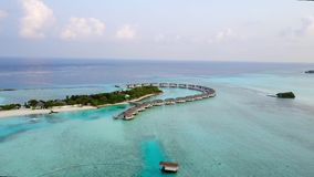 Aerial view of tropical island resort hotel with white sand palm trees and turquoise Indian ocean on Maldives, drone stock video footage