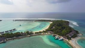 Aerial view of tropical island resort hotel with white sand palm trees and turquoise Indian ocean on Maldives, drone stock footage