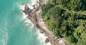 Aerial view of tropical island and sea waves. Aerial drone top view of beautiful tropical island and sea waves crashing coastline cliff  during sunny summer day stock footage