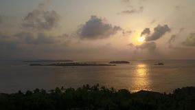 Aerial view of tropical island on sunset, camera is accending over silhouettes of palms and ocean stock video