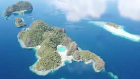 Aerial View of Tropical Islands in Raja Ampat. The scenic limestone islands in Raja Ampat, are surrounded by healthy, shallow coral reefs. This remote, tropical stock video footage