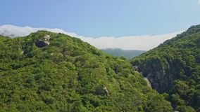 Aerial View Tropical Jungle on Hills White Clouds on Horizon. Fantastic aerial view lush tropical jungle on high hills against blue sky with white clouds line on stock footage
