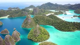 Aerial View of Tropical Lagoon and Islands in Raja Ampat. Rugged limestone islands, surrounded by coral reefs, are found in an idyllic, tropical lagoon in Wayag stock footage