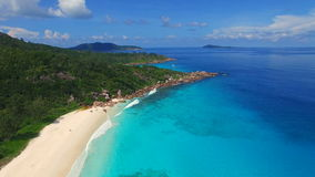 Aerial view of tropical paradise beach with white sand and turquoise water - Grand Anse, La Digue Island, Seychelles. stock video