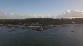 Aerial view of tropical resort and island panorama, Mauritius. Aerial shot of tropical resort on the coast with pier in lagoon and then flying away to show stock footage
