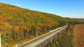 AERIAL VIEW. Truck Driving Along Road Near Autumn. AERIAL VIEW. Camera is moving above asphalt road with one truck driving along near hill with forest in autumn stock footage
