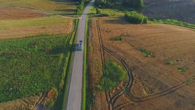Aerial view of truck moving on road in summer field. Flight over road in summer fields stock video