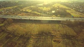 Aerial view of a truck and other traffic driving along a road. At sunrise stock footage