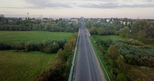 Aerial view of a truck and other traffic driving along a road at sunrise. Beautiful sunset over the road full of traffic. And long river. Great skies. Beautiful stock video footage