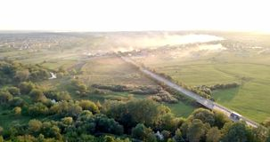 Aerial view of a truck and other traffic driving along a road at sunrise. Beautiful sunset over the road full of traffic. And long river. Great skies. Beautiful stock footage