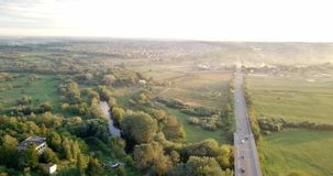 Aerial view of a truck and other traffic driving along a road at sunrise. Beautiful sunset over the road full of traffic. And long river. Great skies. Beautiful stock video