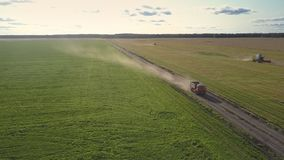 Aerial view truck speeds along ground road making dust cloud. Aerial view orange truck speeds along ground road making dust clouds against gathering wheat stock video