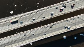 Aerial view of trucks and cars driving on a cable-stayed bridge over the river