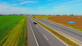 Aerial view trucks and cars driving on country road. Cars driving on highway. Traffic highway aerial landscape. Aerial view trucks and cars driving on highway stock video footage
