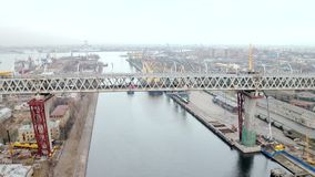 Aerial view of truss bridge above big river at the background of cityscape stock video footage