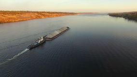 Aerial view of tug boat pushing barge of sand stock footage