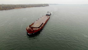 Aerial view of tug boat pushing empty barge stock video footage