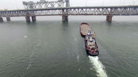 Aerial view of tug boat pushing empty barge.  stock footage