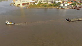 Aerial view of tug boat or ship, container transportation ship on chao phraya river, transportation concept, panning camera shot, stock video