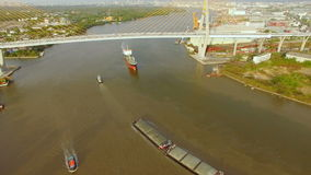 Aerial view of tug boat or ship, container transportation ship on chao phraya river, transportation concept, tilt-up camera shot, stock video footage