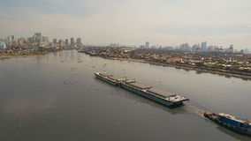 Aerial view tugboat and barge in the sea.Philippines, Manila. Aerial view tugboat pushes barge in the Bay of Manila.Aerial footage Tugboat and ship inside the stock footage