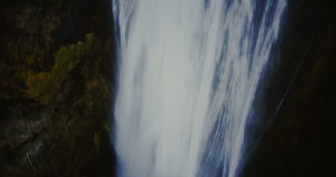 Aerial view of the turbulent flow of water falls down from the top of the mountain. Waterfall Gljufrabui in Iceland. Aerial view of the turbulent flow of water stock footage
