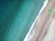 Aerial view turquois water of Ionian Sea in Albania, stones on shore and giant inflated cactus top view.  stock photography