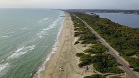 Aerial view of sea beach road trees and water areas under the blue sky. Slow motion. Aerial view of the turquoise sea yellow sand beach with the tourists road stock footage