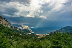 Aerial view from Turunc Bay, with sunbeam and cloudy sky. Marmaris, Turkey. Holiday and summer background. Curvy road and forest. Detail. Panoramic image stock images