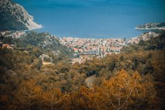 Aerial view from Turunc Bay, with sunbeam and cloudy sky. Marmaris, Turkey. Holiday and summer background. Curvy road and forest. Detail. Panoramic image royalty free stock photos