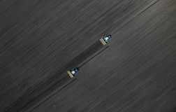 Two bright blue tractors plowing the ground against a black earth background. Top view Stock Images