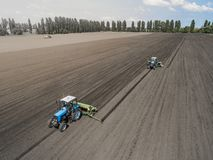 Two bright blue tractor plowing the ground against a black earth background. Royalty Free Stock Images