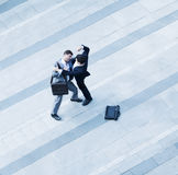 Aerial view of two businessmen fighting each other of the sidewalk Royalty Free Stock Image