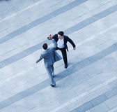 Aerial view of two businessmen giving each other a high five on the sidewalk Stock Images