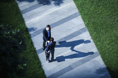 Aerial view of two businessmen shaking hands on the sidewalk stock image